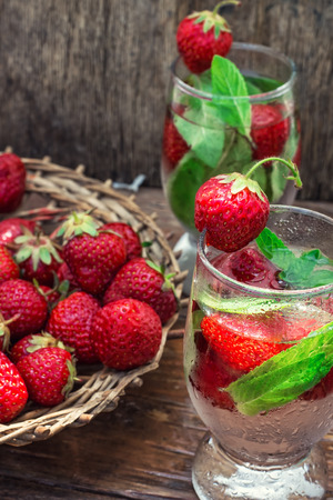 tinted: glass with drink of strawberries and mint on the background of the basket full berries.Selective focus.Photo tinted