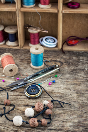 tinted: beadsthreadbuttons craftswomen on wooden background.Selective focus.Photo tinted Stock Photo