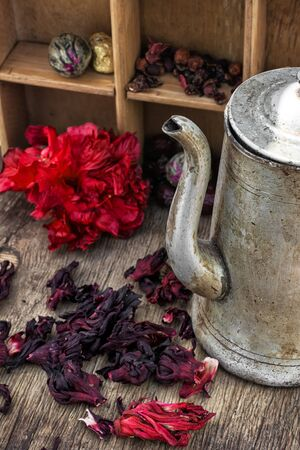 phytotherapy: Hibiscus tea rose and welding on the background of the tea shelves in vintage style.Photo tinted.Selective focus