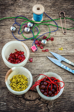 tinted: set of beads in stacks on wooden table with tools for needlework.Selective focus.Photo tinted Stock Photo