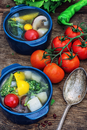 tinted: traditional soup of fresh vegetables in blue pot on wooden background.Photo tinted