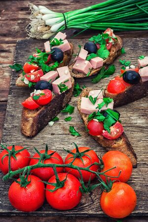tinted: sandwiches with meat fresh tomatoes onions and olives on wooden table top.Photo tinted