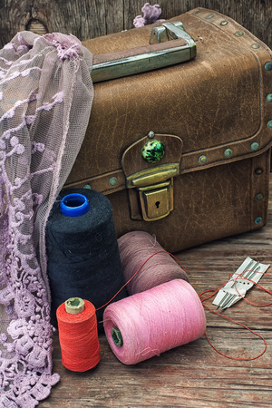 draped cloth: spools of thread on background of old vintage suitcase with draped cloth with lace.Selective focus Stock Photo