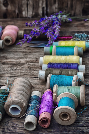 old spools: spools of thread on the old wooden background decorated with branches blossoming lavender.Selective focus