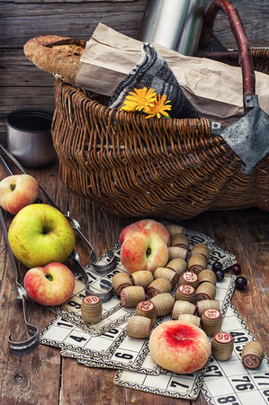 picnic food: Accessories picnic consisting of peaches, apples and lotto games. Stock Photo