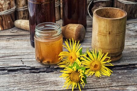 inulin: infusion of inflorescences and roots of the medicinal plant Inula on the wooden table next mortar and pestle Stock Photo