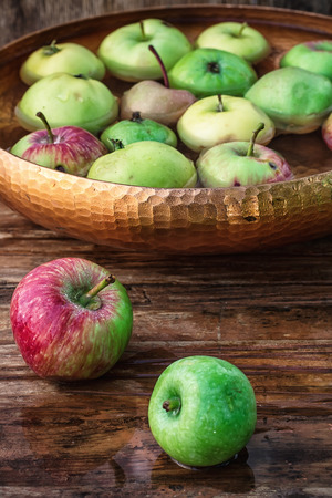 harvest background: Autumn harvest of apples in the bowl of water on wooden background.