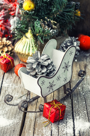 antique sleigh: Christmas sleigh with pine cones and decorations on wooden background.