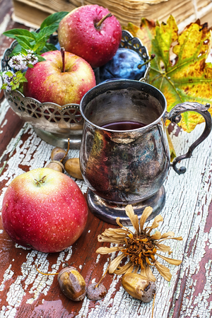 autumn food: mug with herbal tea on background of apples and plums in the autumn garden