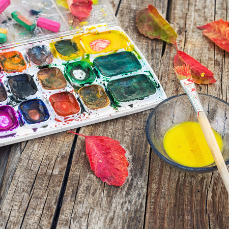 vibrant paintbrush: set of different paint colors and  brush for painting on wooden background in the autumn style Stock Photo