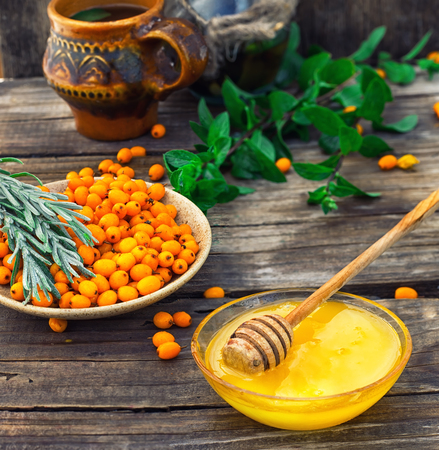 deficiency: Ripe berries of sea buckthorn in  saucer on wooden background Stock Photo