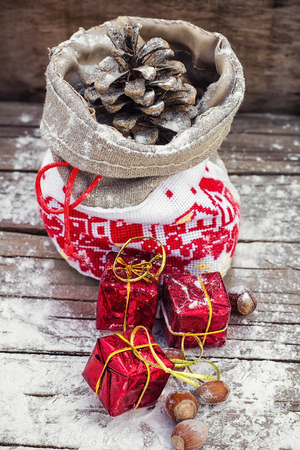 pine three: Symbolic Christmas bag with pine cones and three gift boxes Stock Photo
