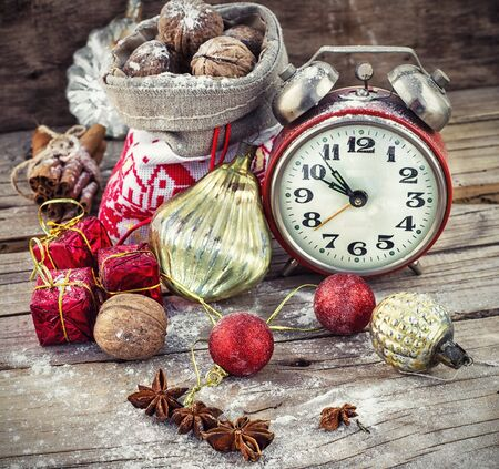 despertador: Un reloj de alarma y la bolsa de frutos secos en el fondo de las decoraciones de Navidad