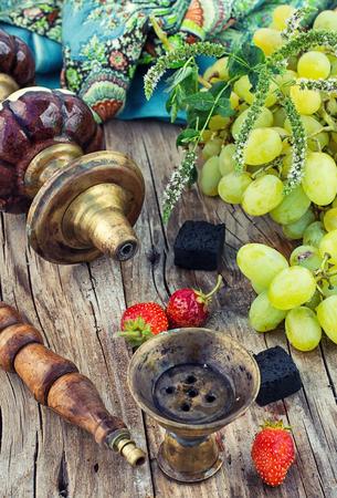 ビンテージ スタイルの木製のテーブルの上の果物風味の水ギセル