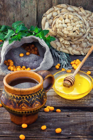 buckthorn: Clay mug with medicinal decoction of sea buckthorn and honey