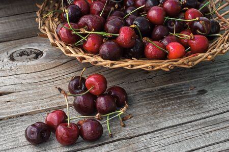 pulpy: Ripe cherries on wooden background in a wicker basket Stock Photo