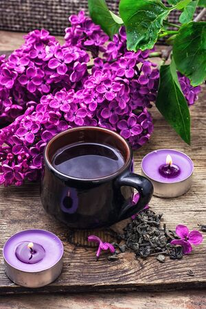 fragrant: Broken fragrant branch with lilac flowers and burning candles. Stock Photo