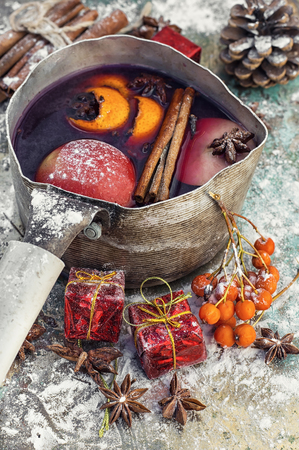 Brewed mulled wine with spices in a stylish pot and Christmas decorations Stock Photo