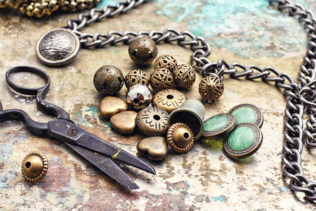 in jewelry: Metal beads,buttons,chain and scissors on retro background Stock Photo