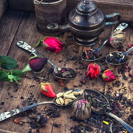 dried herbs: tea brewed in an iron spoon on wooden background with buds of tea roses