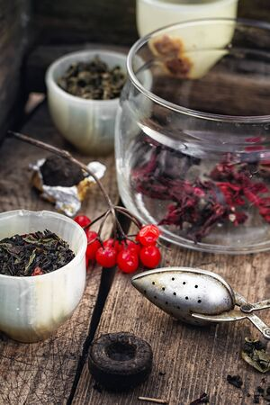 unpressed: trendy cup with tea brewing in the background spoons and viburnum Stock Photo