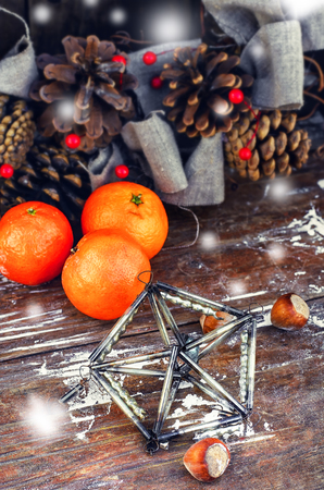 octahedron: Woven Christmas wreath decorated with cones on background of ripe tangerines