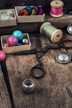 old spools: Old scissors,spools of thread,buttons and beads on wooden table Stock Photo