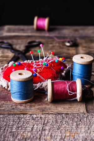 darning needle: pin cushion with needles,thread and buttons for sewing on stylish wooden background Stock Photo