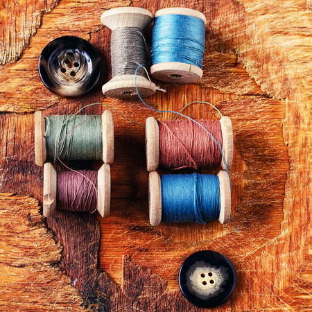 antiquated: Six antiquated sewing thread and buttons on retro background Stock Photo