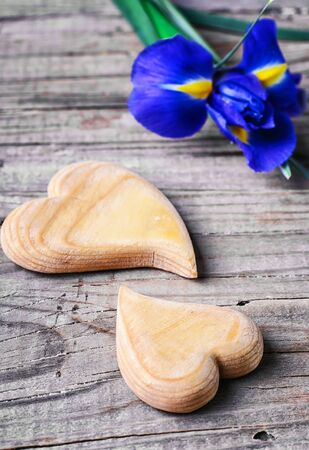 Two symbolic wooden heart on background of fresh flowers Stock Photo