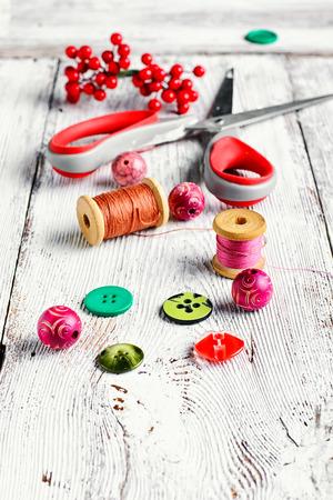 kit de costura: Hilos, botones, cuentas y tijeras en la mesa de la vendimia de la luz Foto de archivo