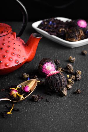 loose leaf: Red teapot and varieties of loose leaf and blooming tea