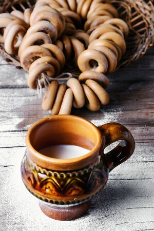 slavic: Bagels and  glass of milk on background strewn with flour in the slavic style Stock Photo
