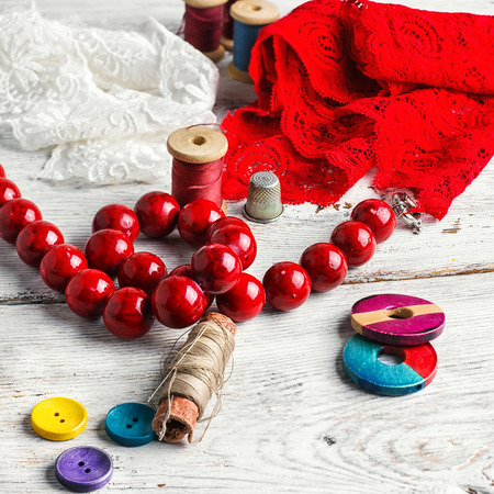 needle laces: Red lace,beads and tools of the artisan jewelry.