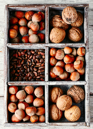cobnut: Wooden box with walnuts and pine nuts and hazelnuts
