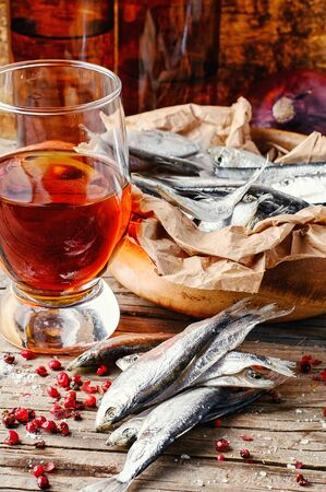 sprat: Glass of beer, smoked sprat, spices in traditional rustic style