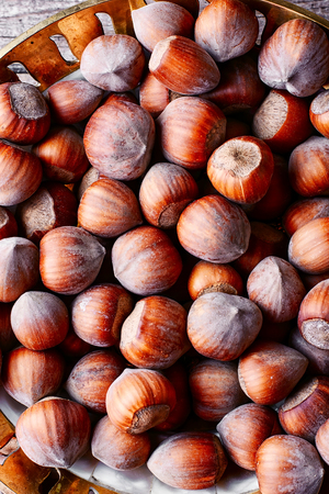 cobnut: Fruits of hazelnut in the copper bowl and scattered near.Top view Stock Photo