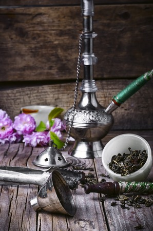 Arab hookah metal and scattered tobacco leaf