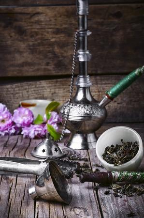 tobacco leaf: Arab hookah metal and scattered tobacco leaf