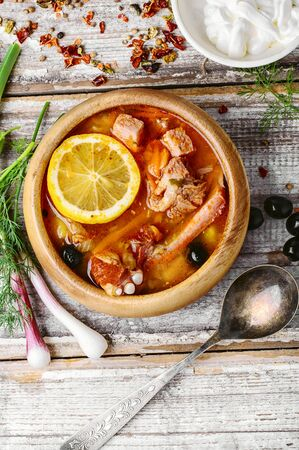 saltwort: Traditional solyanka with smoked meats in wooden plate Stock Photo