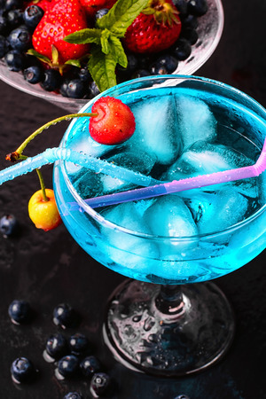 sweet vermouth: glass of blue alcohol cocktail in glass with cherry