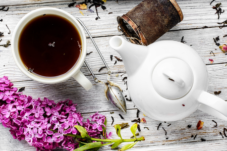 Cup of herbal medicinal tea kettle and bunch of lilac blossoms