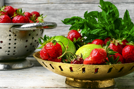 sweet and savoury: Harvest rustic strawberry and lime fruit on light background Stock Photo