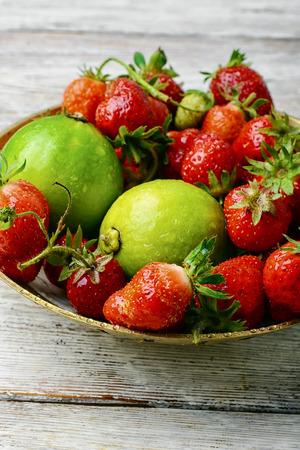 明るい背景に素朴なイチゴとライムの果実を収穫します。