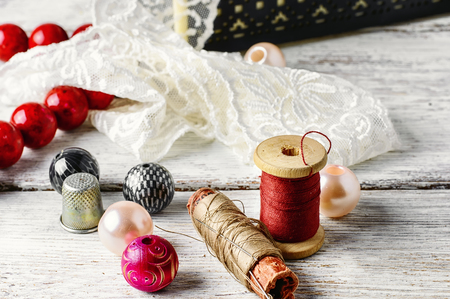 needlework: White lace,spool of thread and beads for needlework