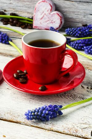 symbolic: Red cup with coffee,flowers hyacinth and symbolic heart Stock Photo