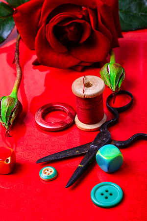 bangles hand: Thread,bead,button, and rose on bright red background Stock Photo