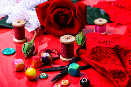 bead embroidery: Thread,bead,button, and rose on bright red background Stock Photo