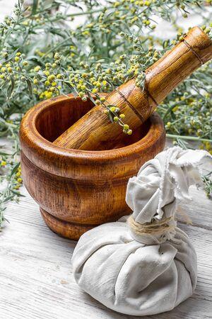 ajenjo: Rama de salvia medicinal y mortero con la maja