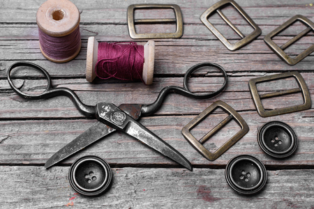 Buttons and fasteners from outdated clothes on wooden background